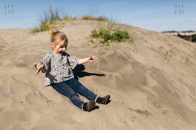 Little girl playing on a sand dune