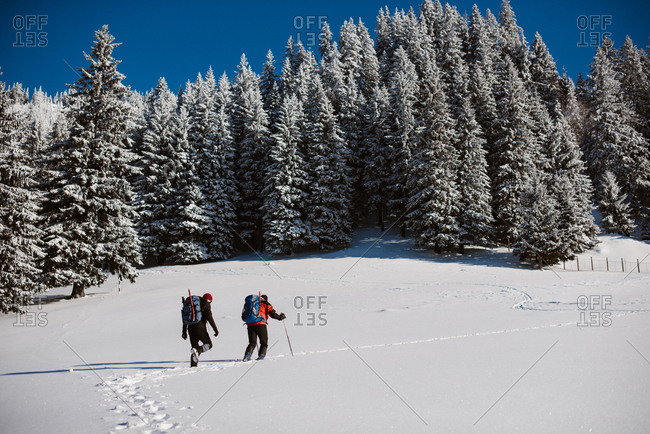 Two people hiking on snowy hill