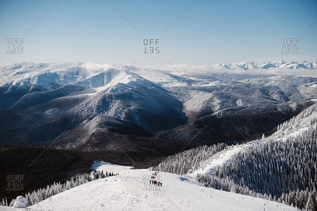 Group of people hiking on snowy hill