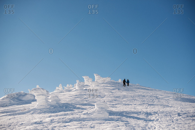 Low angle view of two people hiking on snowy hill