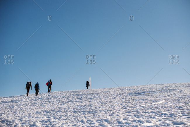 Low angle view of four people hiking on snowy hill