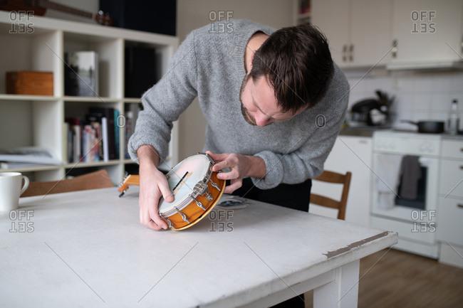 Man repairing his banjo - Offset