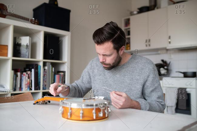 Man replacing strings on his banjo