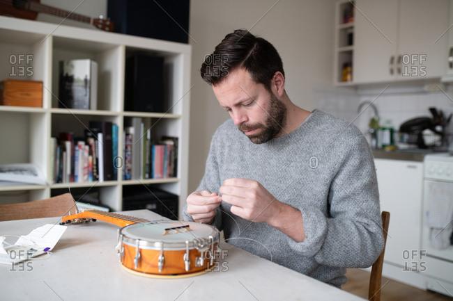 Man fixing strings on his banjo