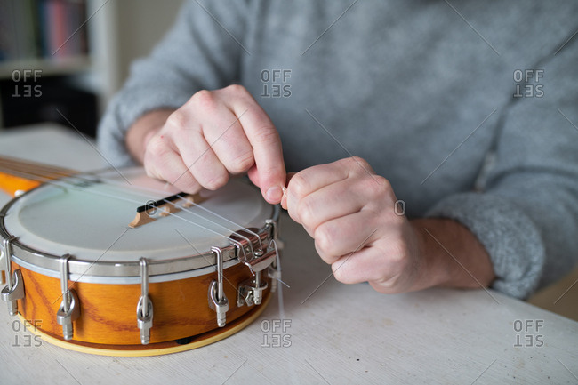 Close up of man replacing strings on his banjo