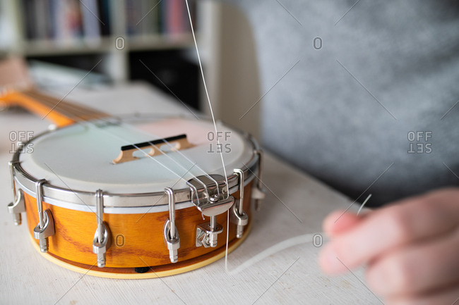 Close up of man fixing strings on his banjo