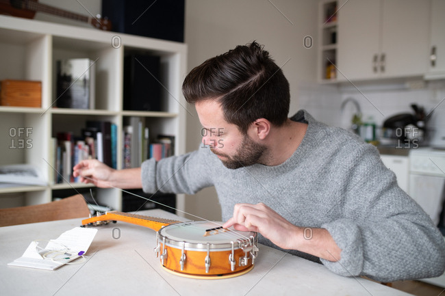 Man replacing the strings on his banjo