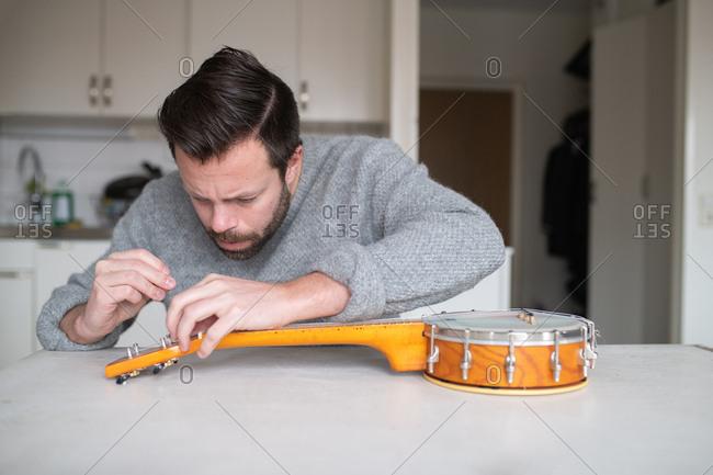 Man fixing his banjo - Offset