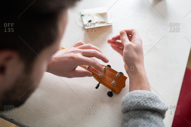 Man replacing a string on his banjo