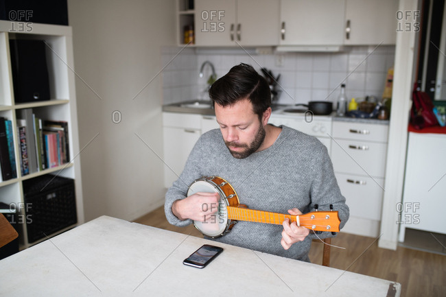 Man tuning his banjo after replacing strings with cell phone app