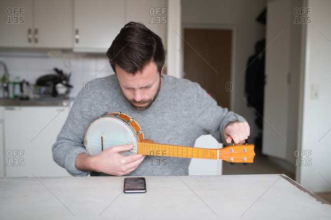 Man tuning his banjo with cell phone app