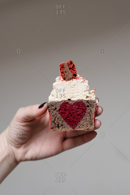 Woman holding a Valentine\'s day themed cupcake cut in half with heart shaped filling in the middle