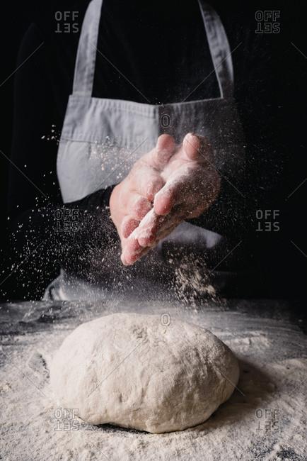 Baker sprinkling flour over ball of dough
