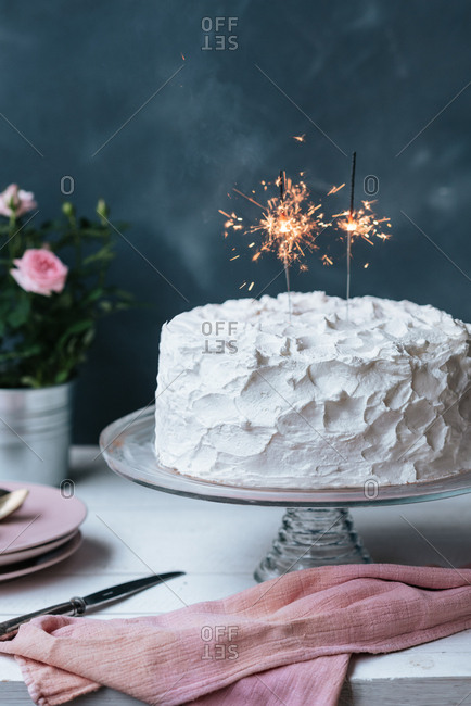 Birthday cake with white whipped cream and sparklers on top