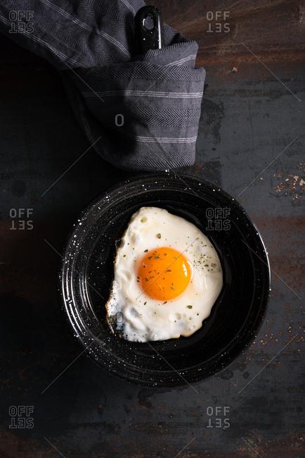 One fried egg in black baking pan on dark background