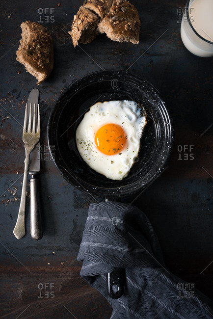 One fried egg in black baking pan on dark background with silverware and bread