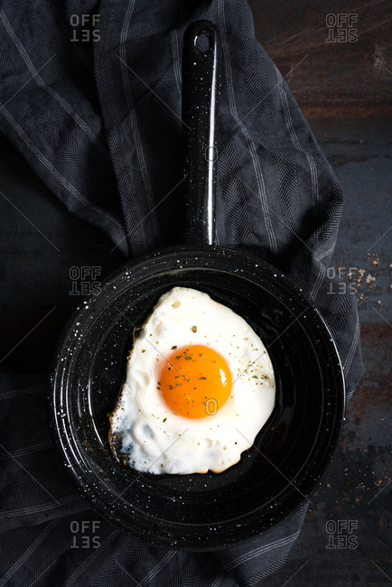 Overhead view of one fried egg in black baking pan on dark background