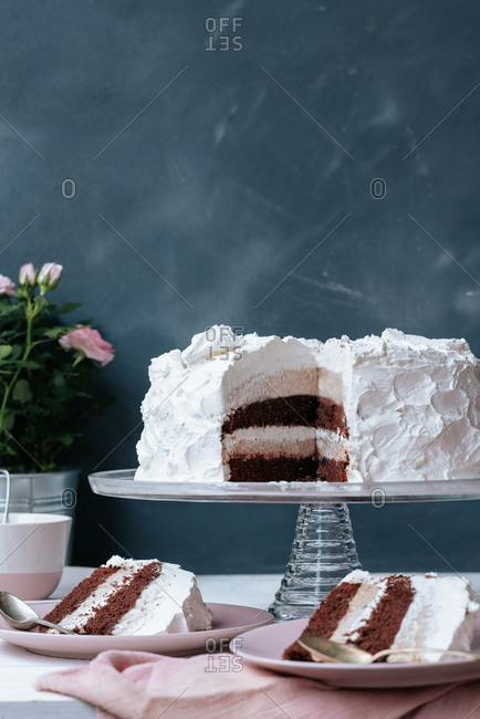Birthday cake decorated with white whipped cream with two cut slices on plates