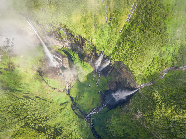 Aerial view above waterfall surrounding by jungle, Faroe Island.