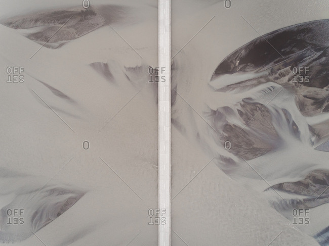 Aerial view above of road crossing a glacial river on the southern region of Iceland.