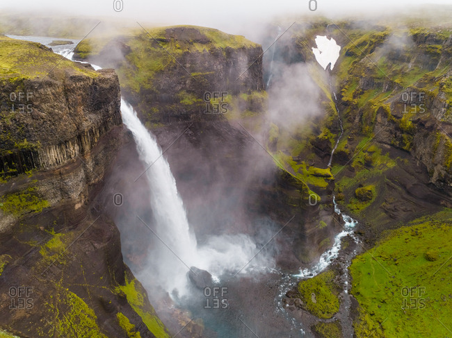 Aerial view of Haifoss waterfall on the southern region of Iceland during a foggy day.