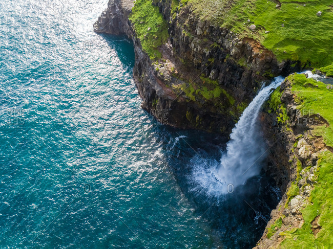 Aerial view of M�lafossur waterfall ending on North Atlantic sea, Faroe island.