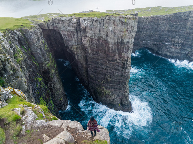 Aerial view of woman standing on the edge of tourists English Slave cliff, Faroe island.
