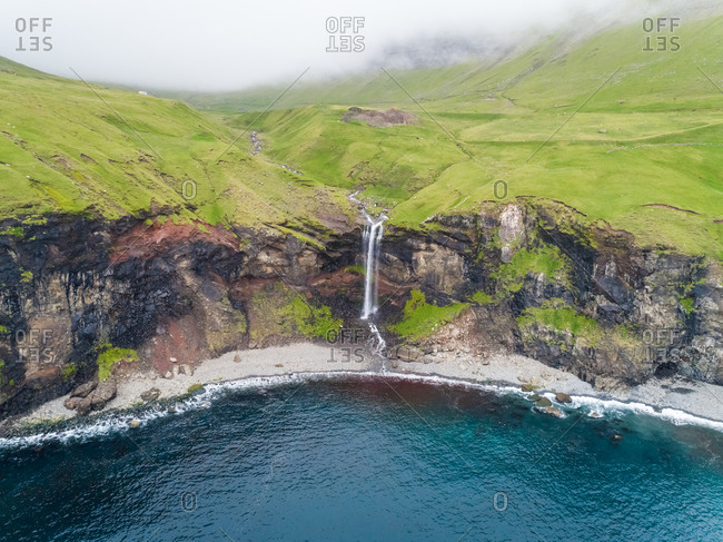 Aerial view of small waterfall ending on North Atlantic sea, Faroe island.