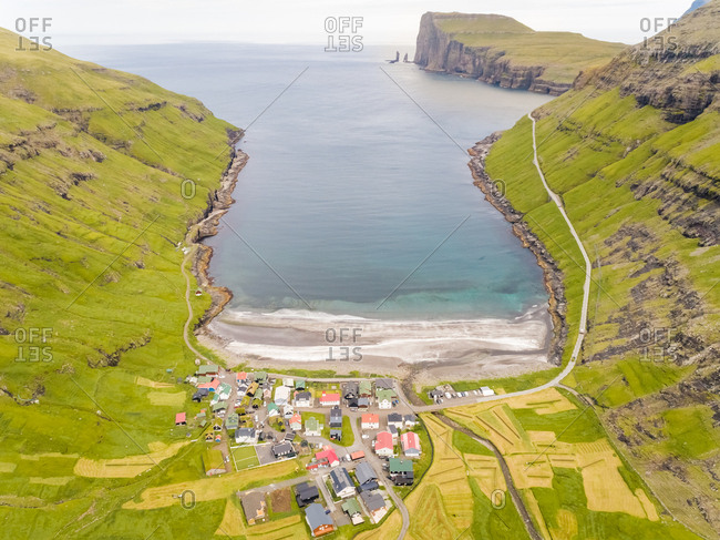 Aerial view of small village surrounding by mountain elevations, Faroe island.