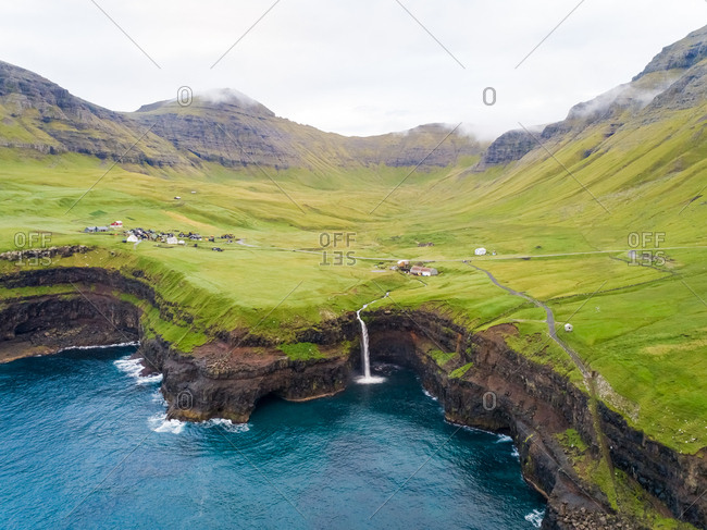 Aerial view faraway of M�lafossur waterfall near a small village, Faroe island.