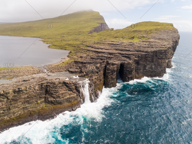 Aerial view of a waterfall near English Slave cliff on North Atlantic sea, Faroe island.