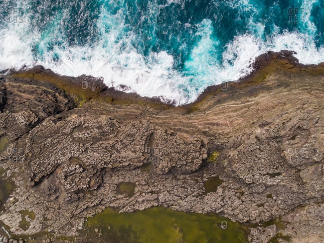 Aerial view of agitated atlantic north sea near rock cliff, Faroe island.