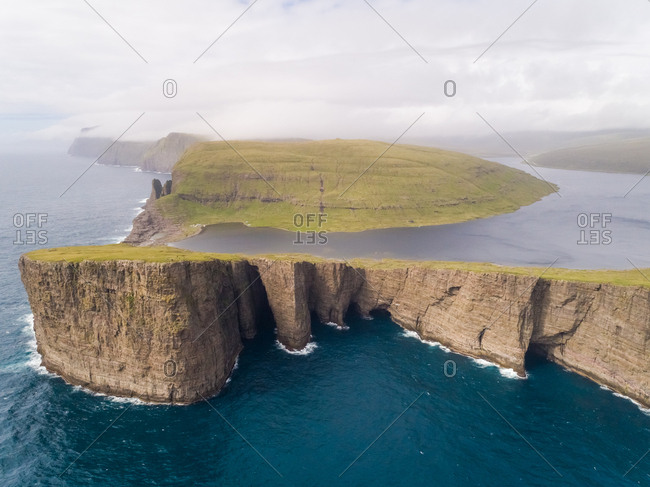 Aerial view faraway of tourists English Slave cliff on North Atlantic sea, Faroe island.