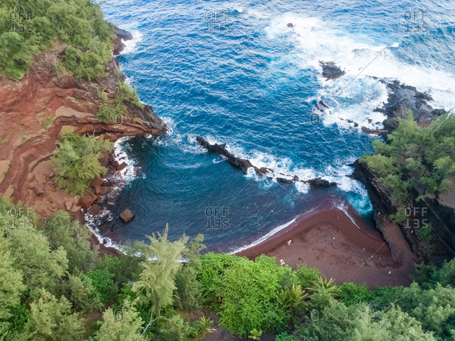 Aerial view of hidden red sand beach surrounding by rainforest, Hawaii, U.S.A.