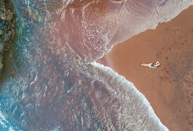 Aerial view of an attractive woman sunbathing on red sand beach, Hawaii, U.S.A.