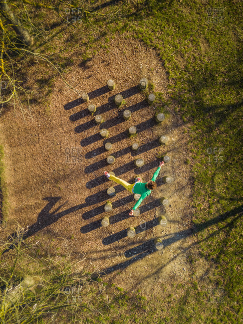 Aerial view of man jumping over wooden stumps, Zagreb, Croatia.