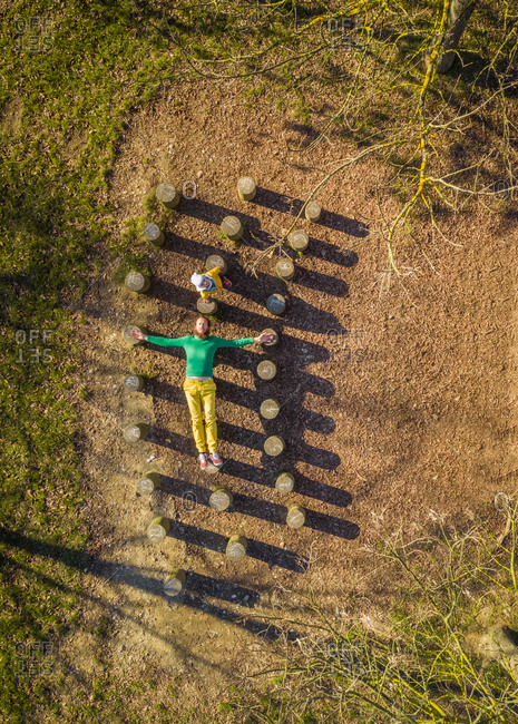 Aerial view of father and infant son over wooden stumps, Zagreb, Croatia.