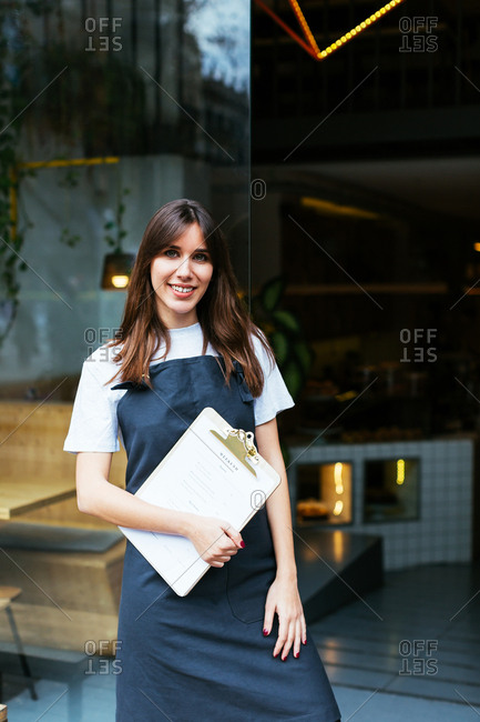 Portrait of a young waitress holding a menu looking at camera.
