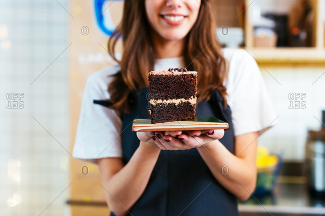 Young waitress serving a piece of cake in a coffee shop.