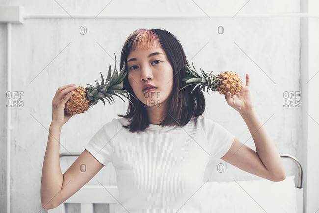 Pretty Asian young girl posing with pineapples and looking at camera.