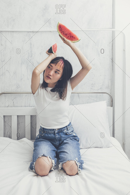 Pretty Asian young woman posing with watermelon.