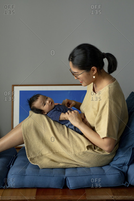 Beautiful Asian woman sitting at home and cuddling her baby daughter.