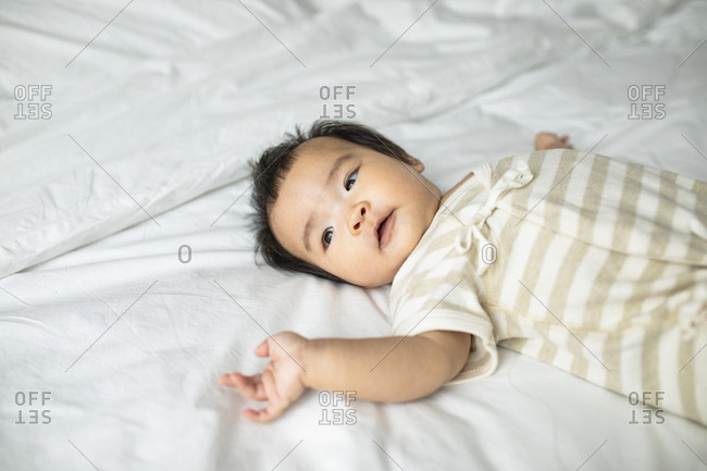 Cute Asian baby girl lying on bed.