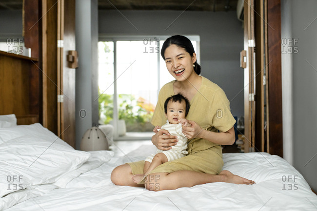 Portrait of beautiful smiling Asian woman sitting on a bed and holding her cute baby daughter.