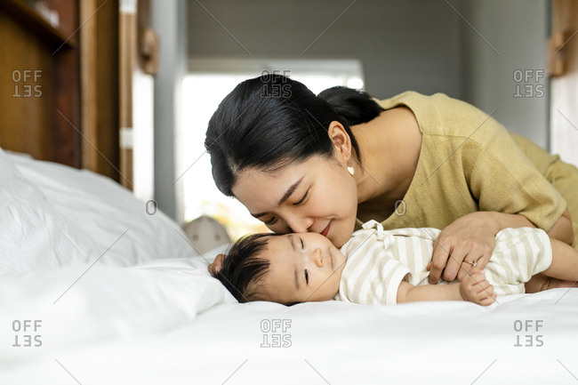 Loving mother kissing her baby on a bed.