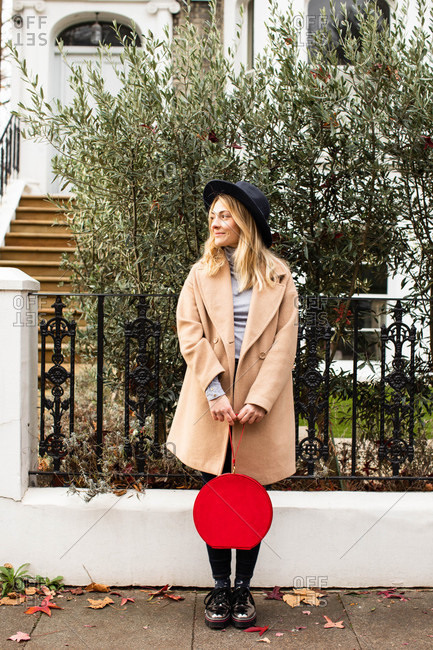 Portrait of pretty stylish blonde woman wearing camel coat and a hat standing outdoors and holding a purse.