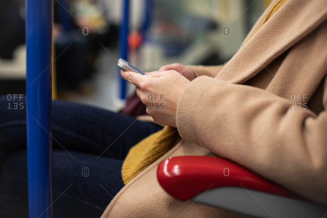 Hands of unrecognizable woman sitting at metro and typing on her cell phone.