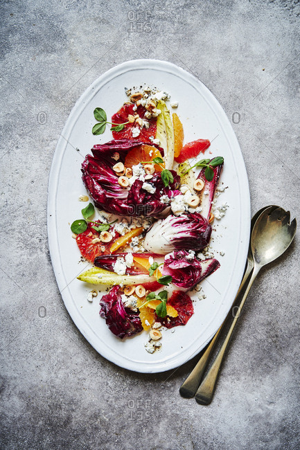 A citrus, chicory, hazelnut and goats cheese salad, shot from above served on a oval white dish with lots of punchy colours. Serving spoons are on the lower right of the image on top of a red cloth.