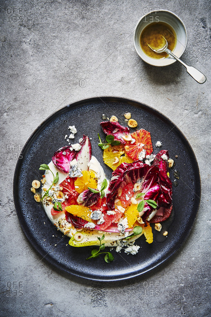 A citrus, chicory, hazelnut and goats cheese salad, sitting atop some yoghurt  and shot from above served on a dark round plate with lots of punchy colours. A ramekin of dressing with a spoon can be found a the top right.