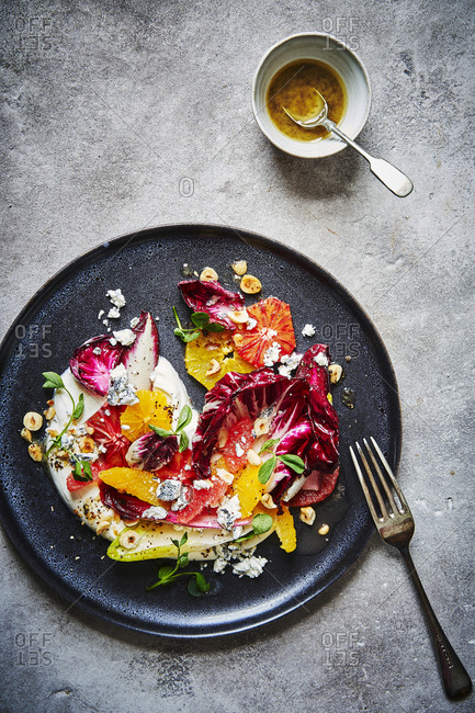 A citrus, chicory, hazelnut and goats cheese salad, sitting atop some yoghurt  and shot from above served on a dark round plate with lots of punchy colours. A ramekin of dressing with a spoon can be found a the top right. The plate is slightly cropped on the left side. A fork is just off the plate ro the lower right.